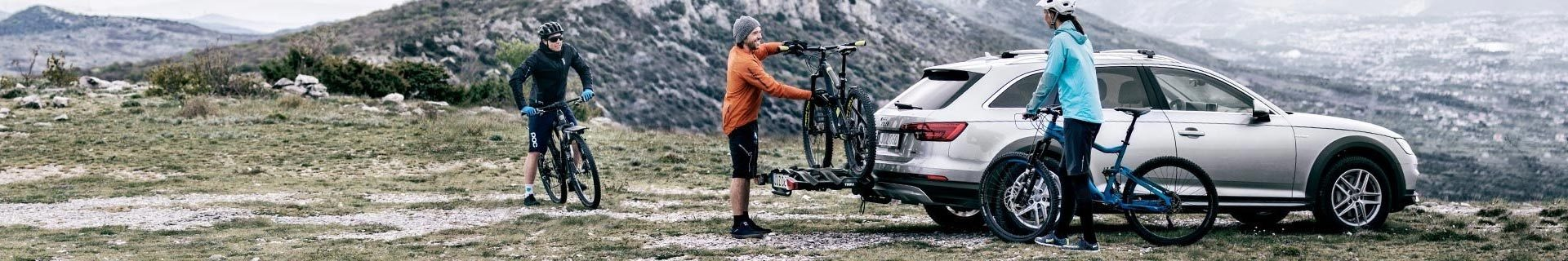 thule bike rack platform with bikes being loaded in alpine area